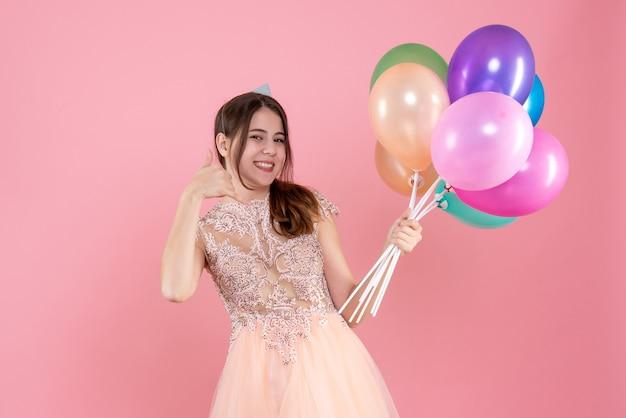 Ragazza felice festa con tappo di partito che tiene palloncini facendo chiamarmi segno di telefono in rosa