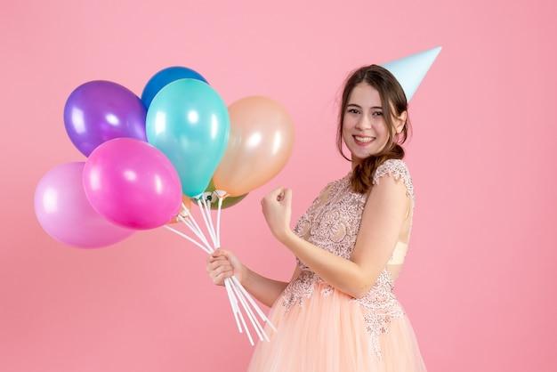 핑크에 풍선을 들고 파티 모자와 함께 행복 한 파티 소녀