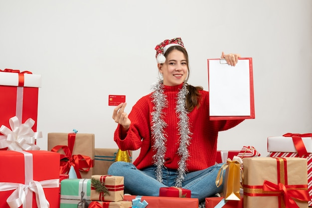 Happy party girl with santa hat holding card and documents sitting around presents on white