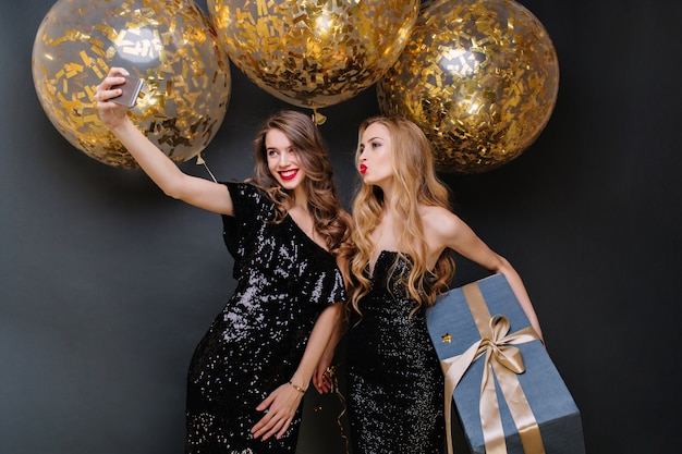 셀카를 만드는 두 명의 유행 젊은 여성의 해피 파티 순간. 럭셔리 블랙 드레스, 긴 곱슬 머리, 황금색 반짝이가있는 큰 풍선, 현재, 재미, 웃고.
