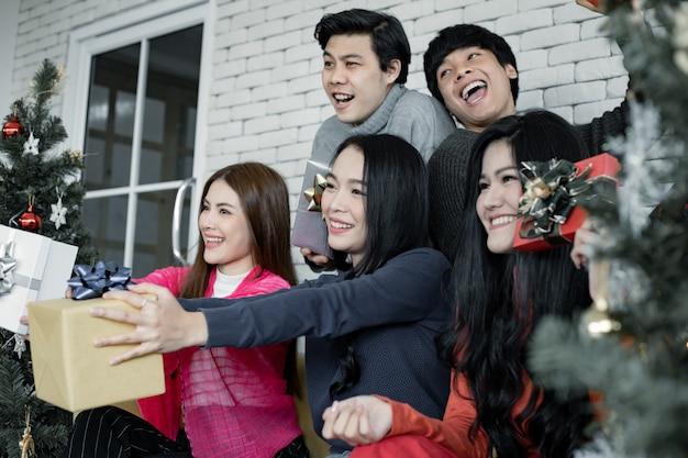 Счастливая вечеринка группы молодых азиатских с подарками дома в праздновании рождественского фестиваля. тайские подростки празднуют рождество и новый год. веселого рождества и счастливых праздников.