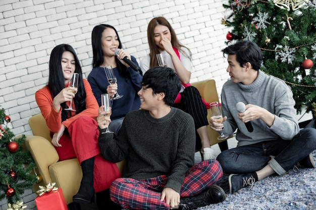 Счастливая вечеринка молодых азиатов с бокалом вина и пением песни дома на праздновании рождества. празднование нового года дома. веселого рождества и счастливых праздников тайской банды подростка.