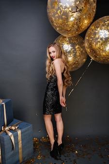 金色のティンセルでいっぱいの大きな風船を持っている長い巻き毛のブロンドの髪で、かかとで、黒い豪華なドレスを着た幸せなパーティータイムのゴージャスな若い女性。プレゼント、お祝い、笑顔。