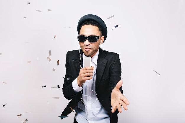 帽子、スーツ、ティンセルで楽しんでいる黒いサングラスでうれしそうなハンサムな男の幸せなパーティータイム。ヘッドフォン、祝う、カラオケ、歌手、スーパースターで音楽を聞く。