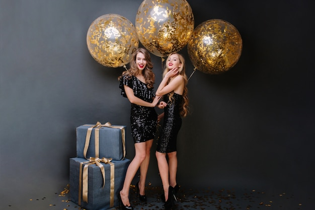 Happy party time of two charming young women in luxury black dresses. long curly hair, attractive look, presents, big balloons with golden tinsels, smiling, having fun.