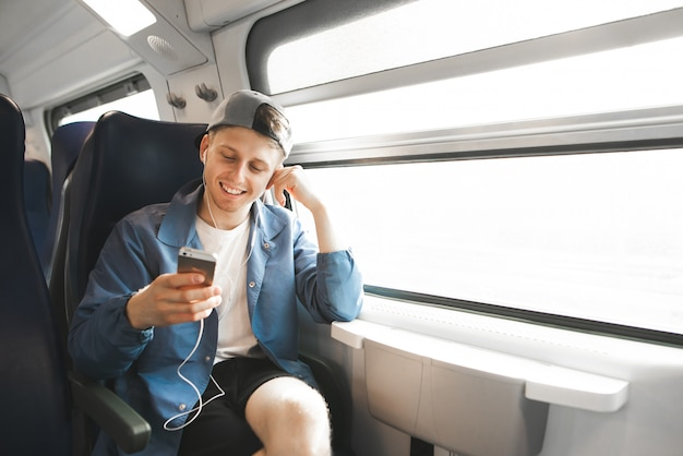 Happy passenger is sitting in the train near the window and uses the internet on the smartphone