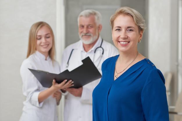Счастливый пациент и врачи позирует, улыбаясь.