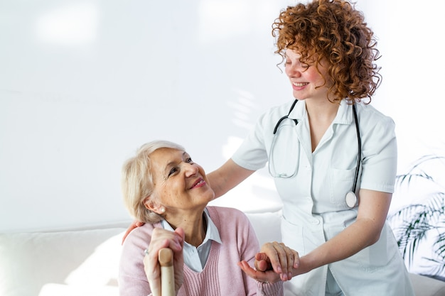 Happy patient is holding caregiver for a hand while spending time together. elderly woman in nursing home and nurse.