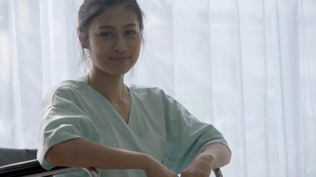 병원 병동에서 부상에서 회복 후 휠체어에 앉아있는 동안 행복한 환자 미소