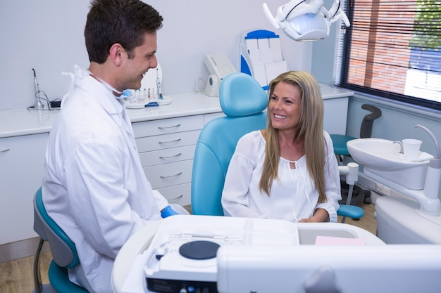 Happy patient talking with dentist