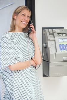 Happy patient using payphone