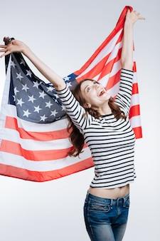 Счастливый патриот. жизнерадостная стройная молодая женщина в полосатом пуловере поднимает за спиной флаг сша и широко улыбается