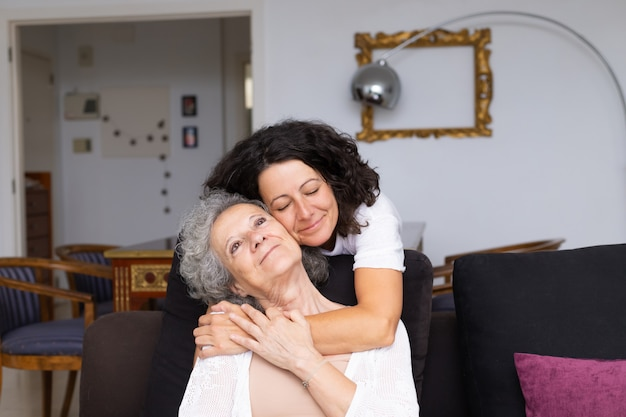 Happy peaceful middle aged woman hugging elderly lady