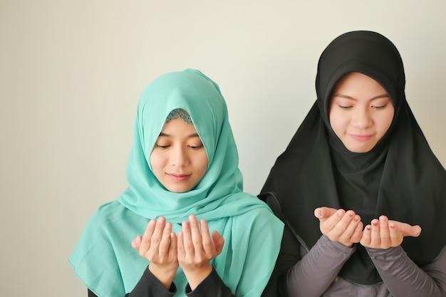 幸せで平和なイスラム教徒の女性のラマダンが祈り、イスラムの女性が瞑想します。イスラム教徒の女の子の瞑想;信仰を祈る忠実なアジアのイスラム教徒の女性。イスラム教、イスラム教の儀式、イスラム教のラマダンの概念
