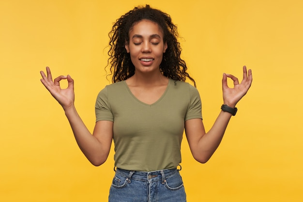 Happy peaceful young woman with eyes closed in casual clothes meditating and practicing yoga isolated over yellow wall
