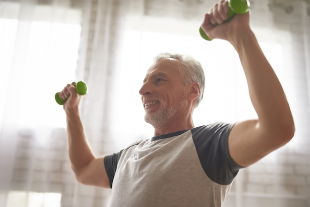 Happy pensioner doing dumbbells exercises at home.