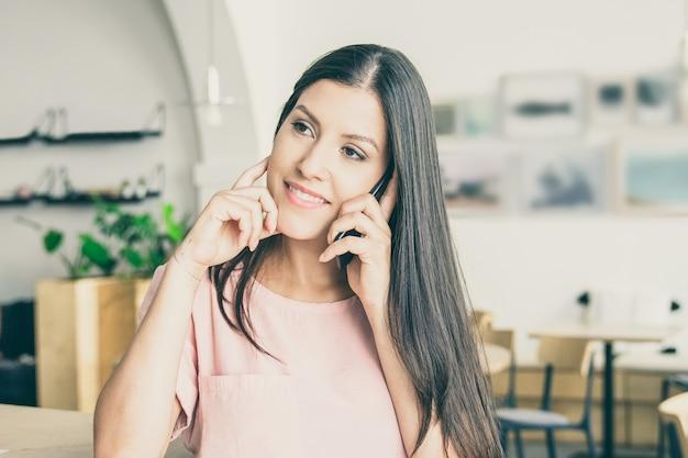 Счастливая задумчивая молодая женщина разговаривает по мобильному телефону, стоя в коворкинге, опираясь на стол, глядя в сторону и улыбаясь