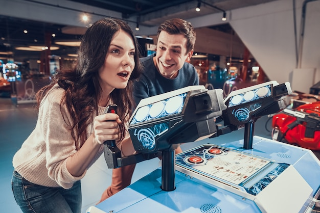 Happy people are piloting spacecrafts playing in arcade.