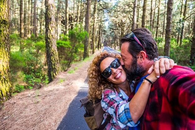 긴 아스팔트 도로에 숲에서 함께 여행하는 야외 여가 활동을 즐기는 행복한 사람들 백인 부부
