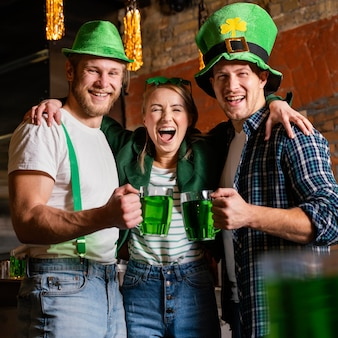 Happy people celebrating st. patrick's day at the bar with drinks