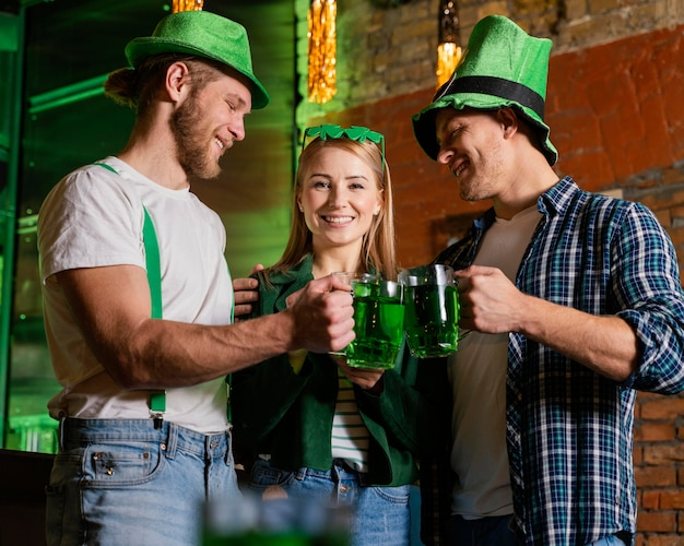 Happy people celebrating st. patrick's day with drinks