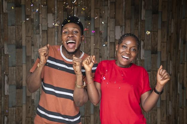Gente felice che festeggia con i coriandoli davanti a una parete di legno
