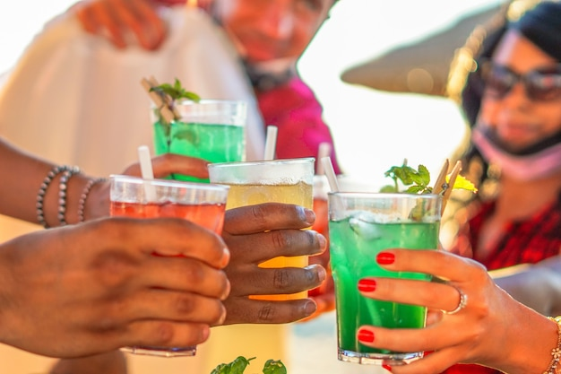 Happy people cheering with mojito and having fun - multiracial friends drinking coktails in a beach bar outside in summer days with face mask on to be protected from coronavirus