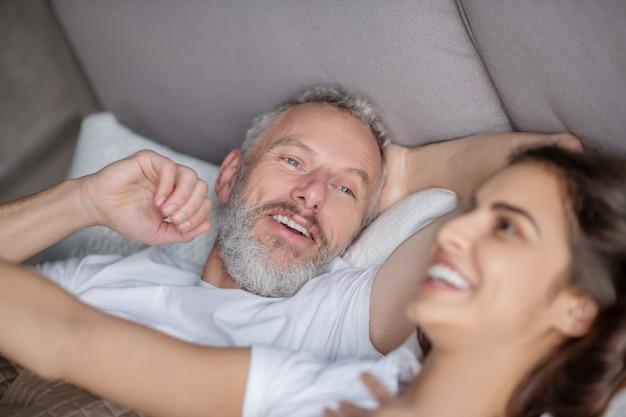 幸せな人々。白髪のひげを生やした男性とベッドに横たわっている黒髪の熱狂的な女性の幸せそうな顔のクローズアップ
