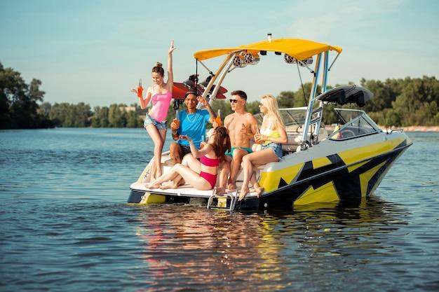 행복한 사람들. 맑은 여름날 요트에서 즐거운 시간을 보내고 쾌활한 젊은 사람들의 회사