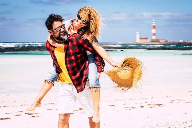 幸せな人々のカップルは、一緒に笑って楽しんでいる関係と夏休みの休暇を楽しんでいます-男性は女性を運び、愛と友情を持ってビーチの屋外レジャー活動を楽しんでいます