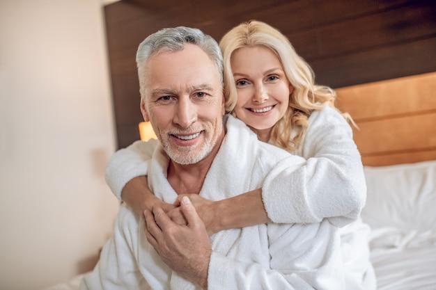 행복한 사람들. 목욕 가운을 입은 커플은 함께 시간을 즐기고 행복해 보입니다.