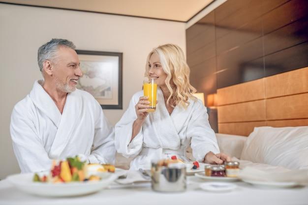 Счастливые люди. пара в банных халатах наслаждается временем вместе и выглядит счастливой