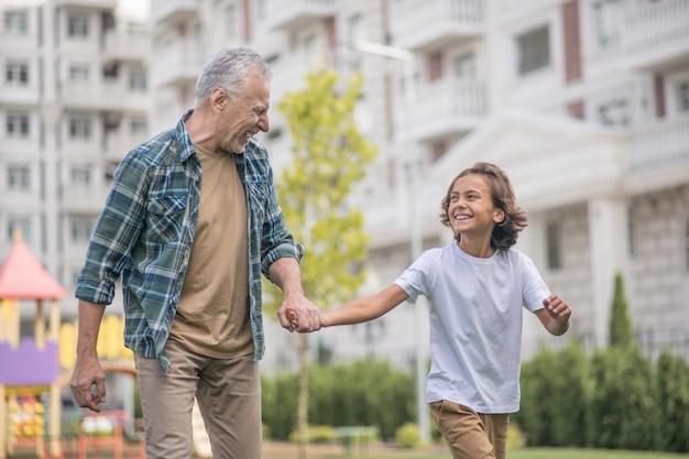 Счастливые люди. папа и сын гуляют вместе рука об руку и выглядят счастливыми
