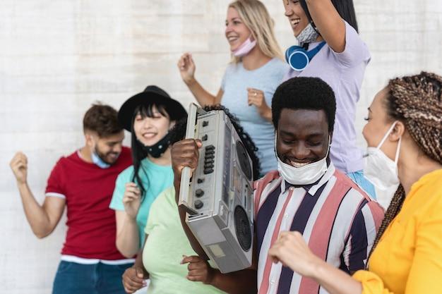 古いラジカセステレオから音楽を聴きながら屋外で踊る幸せな人々