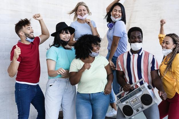Счастливые люди танцуют на открытом воздухе, слушая музыку из старого стерео бумбокс