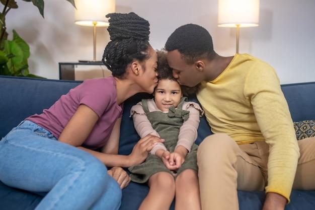 행복한 사람들. 어두운 피부의 젊은 성인 엄마와 아빠는 집에서 소파에 앉아 부모 사이에 앉아 있는 귀여운 딸에게 키스를 합니다.