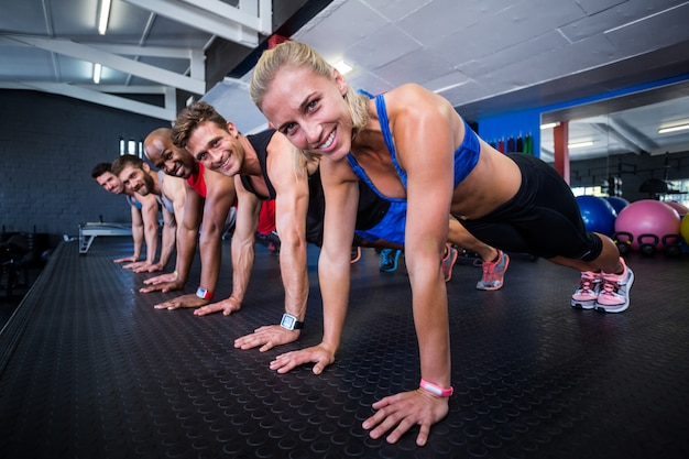 Happy people doing push-ups in gym