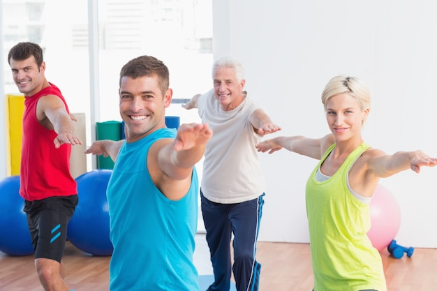 Happy people doing warrior pose in yoga class