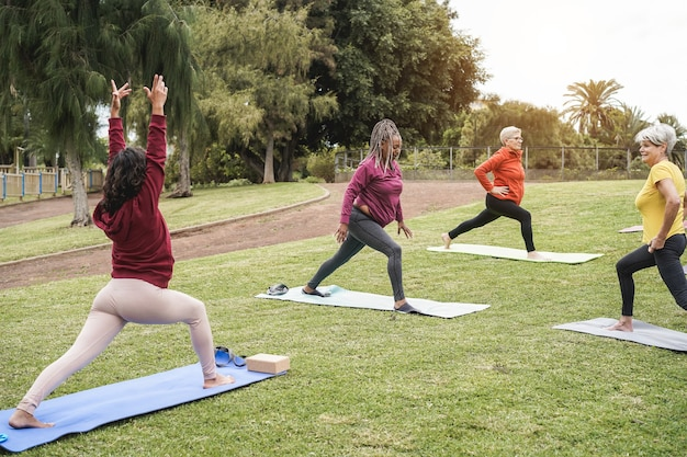 Happy people doing yoga class at city park