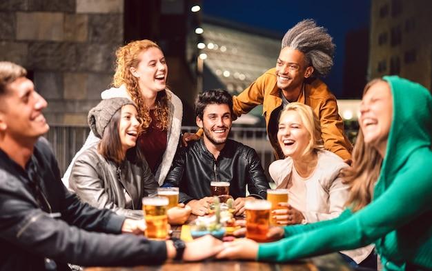 Счастливые люди пьют пиво в баре пивоварни на открытом воздухе