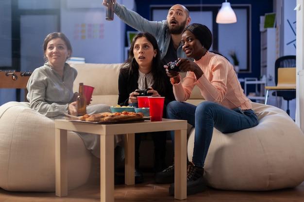 コントローラーのジョイスティックを使用しながら、オフィスで仕事をした後、コンソールでゲームを楽しんでいる幸せな人々。労働者の多民族グループは、屋内でのパーティーのお祝いで楽しい娯楽のために遊びます