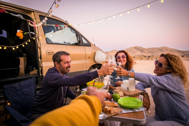 Happy people group of friends toasting and enjoying the travel vacation together - cheerful. woman and man with food in outdoor leisure activity - modern van and ocean