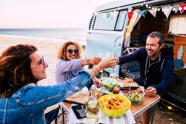 Happy people group of friends toasting and enjoying the travel vacation together - cheerful. woman and man with food in outdoor leisure activity