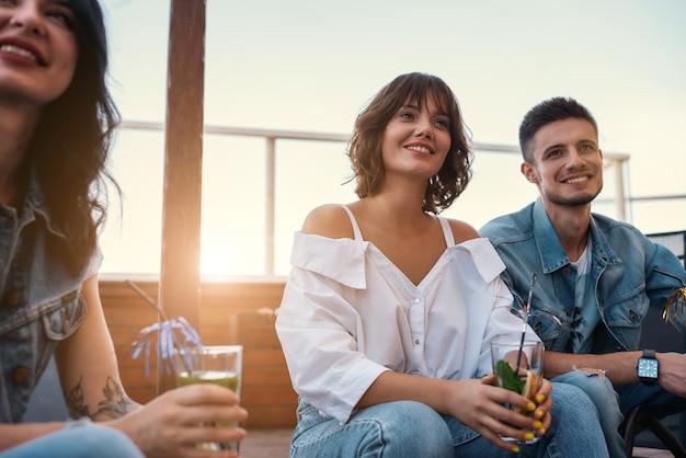 Группа счастливых людей, пьющих коктейли и проводящих время вместе