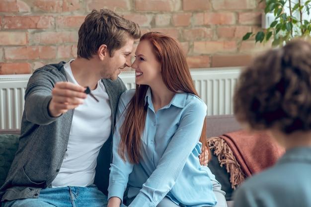 Счастливые люди. счастливый молодой взрослый мужчина держит ключ от нового дома, обнимая милую жену с длинными волосами, сидя перед брокером в офисе