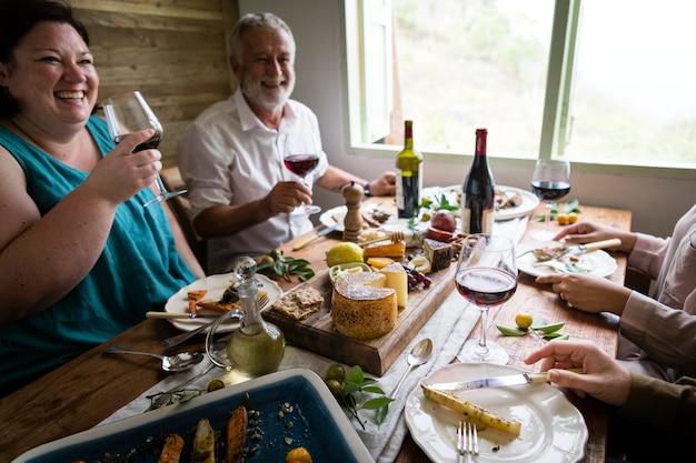Счастливые люди, имеющие сырное ассорти и вино