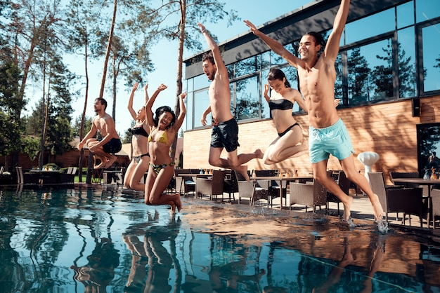Happy people having fun by jumping from poolside into water.