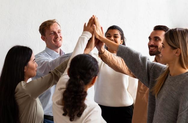 集団療法のセッションでお互いにハイタッチする幸せな人々