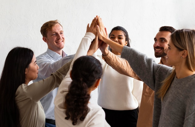 Happy people high-fiving each other at a group therapy session