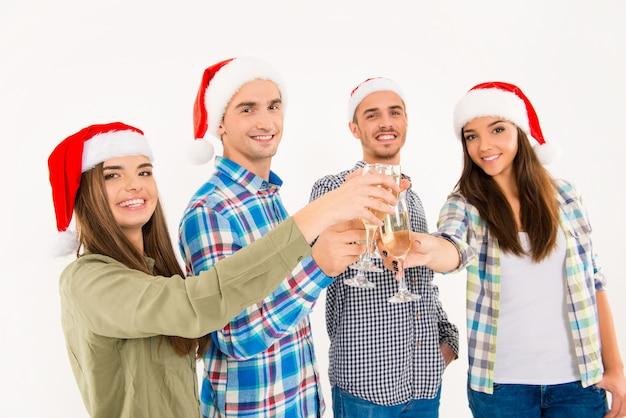 Счастливые люди в шляпах санта-клауса празднуют рождество с шампанским